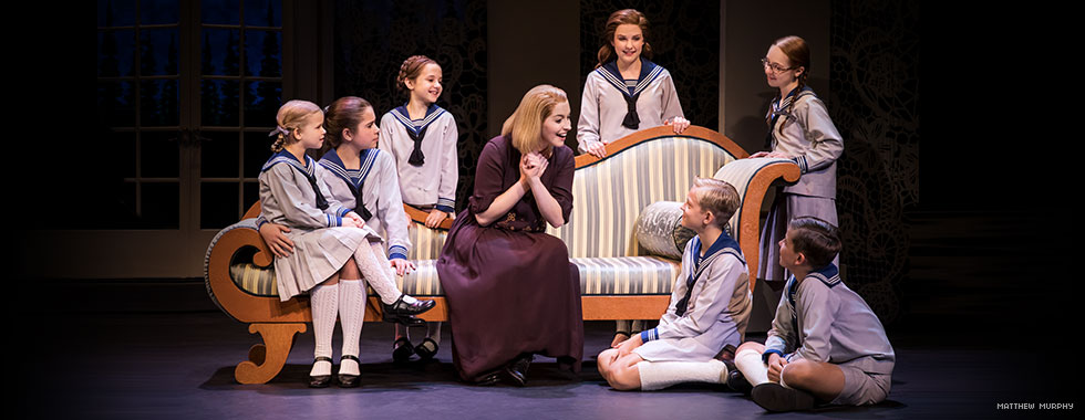 Maria, sitting on a chaise lounge with her hands clasped together in joy, speaks to the von Trapp children as they attentively gather around her.