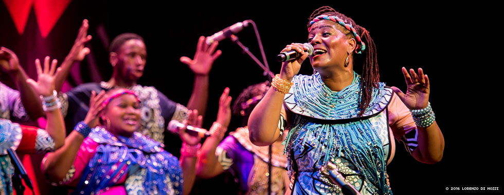 A woman wearing a braided headband, bracelets, and a dress adorned with beads sings while a members of a chorus in the background raise up their arms.