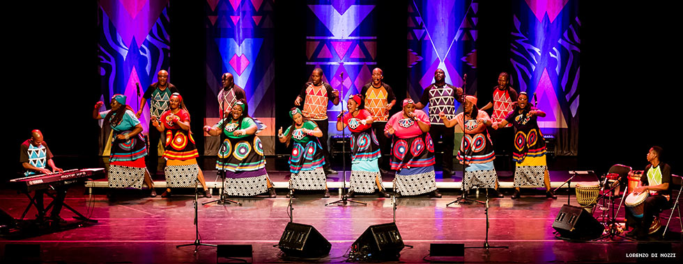 A chorus of men and women wearing costumes featuring similar designs sing and dance while a keyboardist and congo drummer perform on opposite ends of the group.