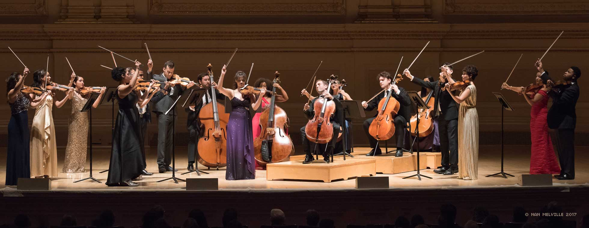 18 string musicians stand across the stage with their bows in the air.