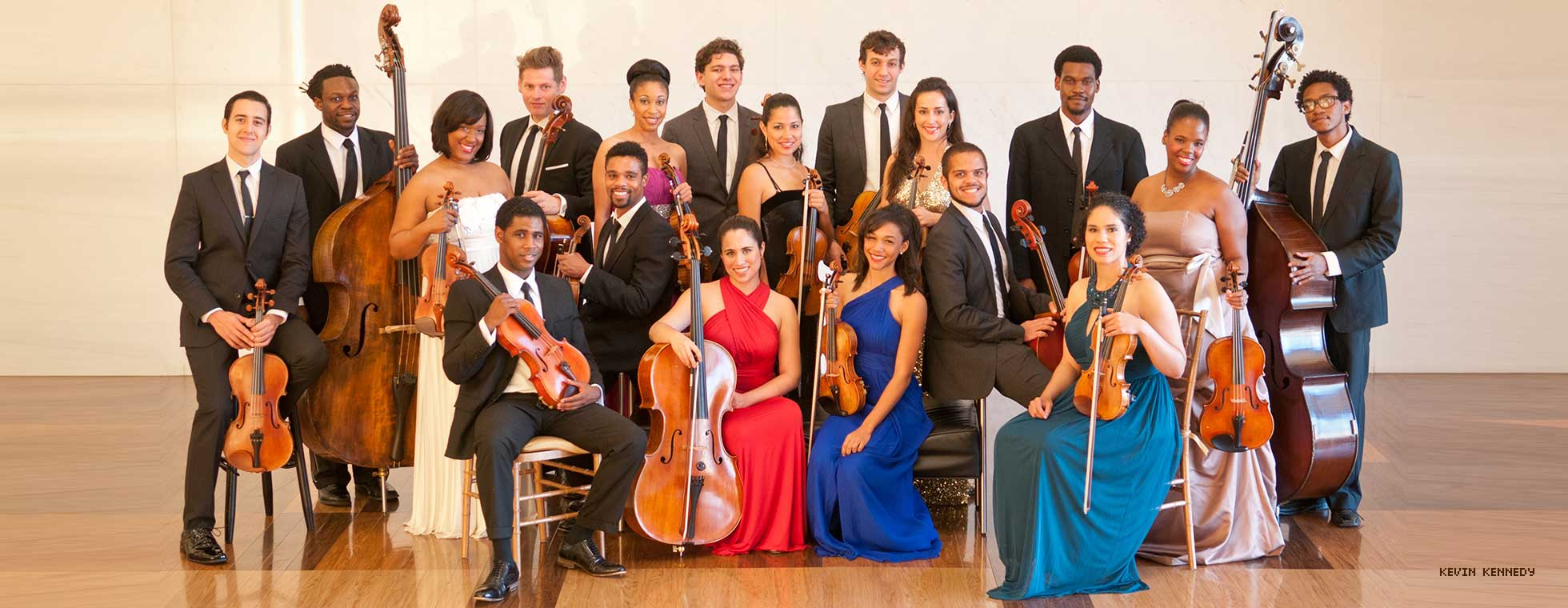 18 musicians in formal attire stand together as a group with their instruments.