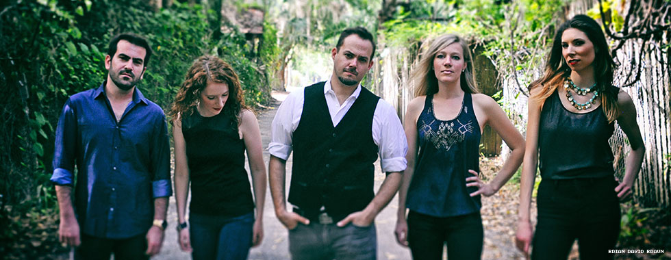 Two men and three women stand in a row along a dirt road surrounded by trees.