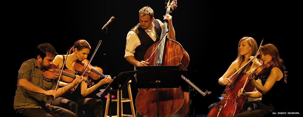A man playing the cello stands in the center of a dark stage with a second man and three women playing various stringed instruments around him.