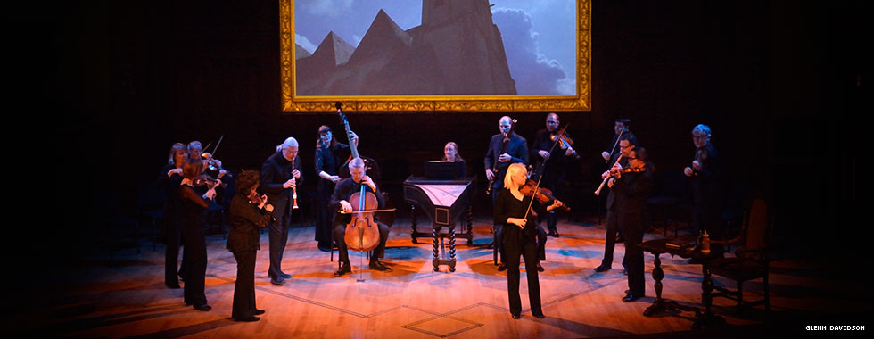 Seventeen visible members of Tafelmusik Baroque Orchestra, dressed similarly, are illuminated under a spotlight while they stand on a stage below an oversized framed picture of a cathedral.