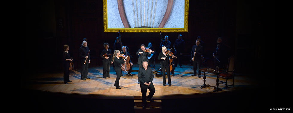 The classical musicians of Tafelmusik Baroque Orchestra, dressed similarly, play their instruments as a man, holding one hand in another in front of him, descends steps leading away from the stage.