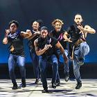 Five step dancers perform in a row on stage.