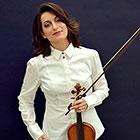 A woman holds a violin and bow in her left hand and rests her right hand on her hip.