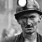 A coal miner dusted with coal soot and wearing a hardhat with lamp looks blankly at the camera in a historic photo.