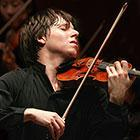 A violinist closes his eyes and throws his head back while he plays a violin.