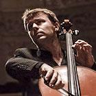 A cellist looks upward as plays his instrument.