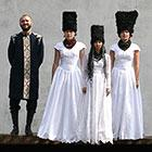 The members of DakhaBrakha, dressed in traditional-style Ukraine folk costumes and tall lamb's wool headgear, stand for a photo.