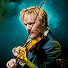 A man plays his violin while a light haze surrounds him on stage.