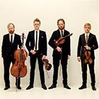 Four men stand in a row holding stringed instruments.