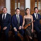 A quartet—three men wearing suits and a woman holding a violin and dressed in a simple formal dress—sit for the camera.