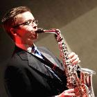 A young man plays the saxophone.