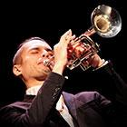 A man wearing a suit closes his eyes as he plays a trumpet pointed upward.