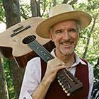A man smiles as he slings his guitar over his right shoulder.