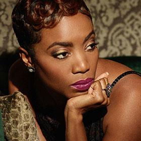 Heather Headley lounges on pillows with her hand supporting her head.