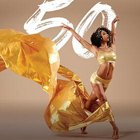 A female dancer raises her arms in the air as a plume of golden fabric flows in her wake.