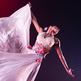 A dancer extends her arms as she spins around.