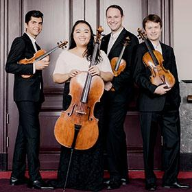 Members of the quartet stand together wearing formal attire and holding their instruments.