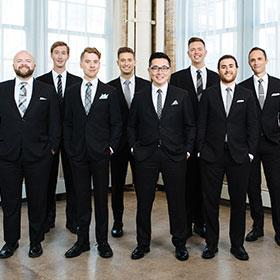 The eight members of Cantus stand in a row wearing black suits.