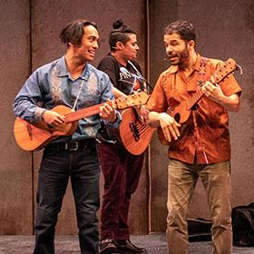Three Latinx guitarists play and sing.