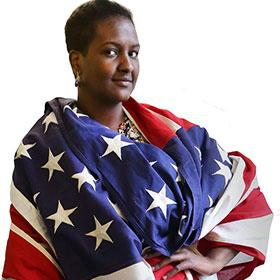 Sharifa Ali stands draped in the flag of the United States.