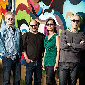 Quartet members wearing sunglasses stand against a mural wall.