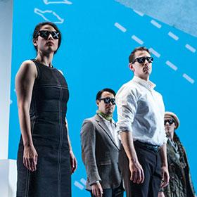 Actors walk across the stage wearing sunglasses while charts and maps are projected onto them.