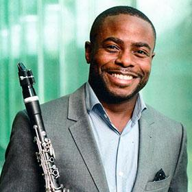 Anthony McGill holds his clarinet to his shoulder and smiles.