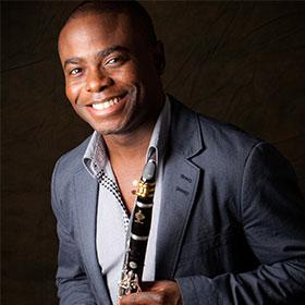 Anthony McGill smiles at the camera while holding his clarinet.