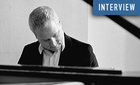 Photo of Jeremy Denk playing the piano.