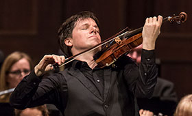 Bell plays the violin with his eyes shut in front of an orchestra.