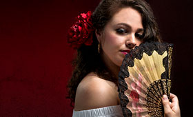 A young woman holds a fan.