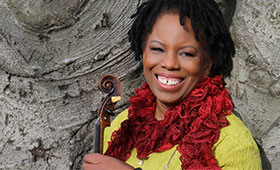 Regina Carter smiles with her violin.