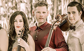 A young woman with her violin stands with a man with a cello and another man with a violin on his shoulder.