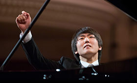Cho sits at the piano with his arms raised as he finishes performing.