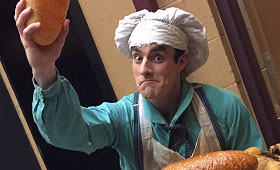 Cullen, dressed as a baker, holds up a loaf of bread from his basket.