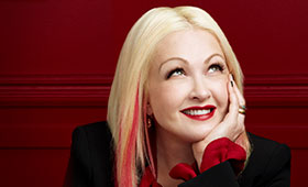 Cyndi Lauper rests her chin in her hand while looking up.