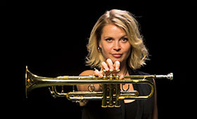 Bria Skonberg holds her trumpet in front with her arm extended.