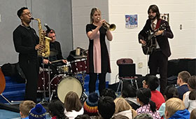 Musicians perform in front of an assembly room full of children.