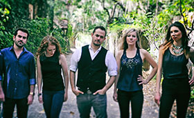 Two men and three women stand on a dirt road surrounded by trees.