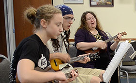 Three collective members play ukuleles. The farthest member sings.