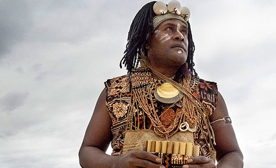 A musician wearing traditional native costume looks out into the ocean holding a wooden wind instrument.