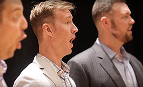 Three men shown in a profile view sing.
