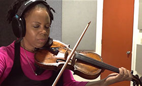 A woman in a recording booth closes her eyes and wears headphones as she plays a violin.