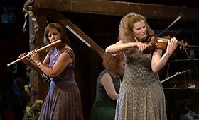 A woman plays the flute on the left of the stage and to the right a second woman plays the violin.