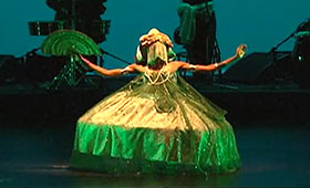 A female dancer, wearing a traditional Brazilian headdress and tent-style gown, outstretches her arms and legs while she holds a fan in her right hand during a folk dance.