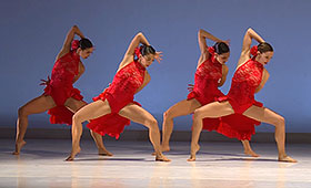 Four female dancers wearing similar flowing dresses each stand with knees bent at ninety degrees and their right arms stretched up with their hands behind their heads.